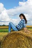 Donna di Yoing in mucchi di fieno sui campi Immagini Stock