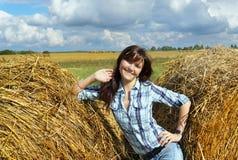 Donna di Yoing in mucchi di fieno sui campi Fotografia Stock Libera da Diritti