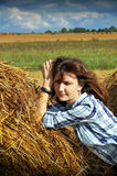 Donna di Yoing in mucchi di fieno sui campi Fotografie Stock Libere da Diritti