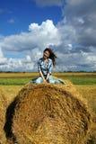 Donna di Yoing in mucchi di fieno sui campi Immagine Stock