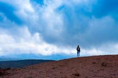 Donna di Yong che gode del paesaggio ultraterreno del vulcano di Etna, Sicilia immagini stock