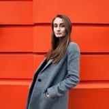 Donna di Yound sulla parete arancio Fotografia Stock Libera da Diritti
