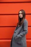 Donna di Yound sulla parete arancio Immagini Stock Libere da Diritti