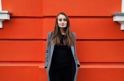 Donna di Yound sulla parete arancio Fotografia Stock