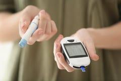 Donna diabetica che tiene glucometer digitale fotografia stock