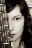 Donna dietro il fretboard della chitarra Fotografie Stock