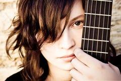 Donna dietro il fretboard della chitarra fotografia stock libera da diritti