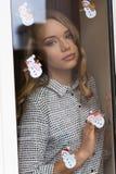 Donna dietro la finestra nell'orario invernale Immagini Stock