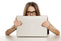 Donna dietro un computer portatile Fotografia Stock