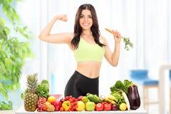 Donna dietro una tavola con la frutta e le verdure fotografie stock libere da diritti