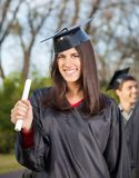 Donna in diploma della tenuta dell'abito di graduazione sopra Immagini Stock