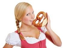 Donna in dirndl che mangia ciambellina salata Fotografia Stock