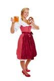 Donna in dirndl con birra e la ciambellina salata Fotografia Stock