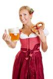 Donna in dirndl con la birra d'offerta della ciambellina salata Fotografia Stock