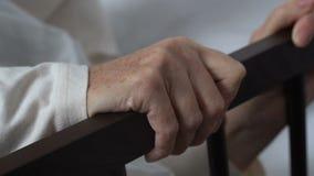 Donna disabile anziana che prova a stare su dal letto di ospedale, centro di riabilitazione stock footage