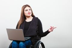 Donna disabile con il computer portatile sulla sedia a rotelle immagini stock libere da diritti