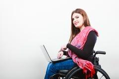 Donna disabile con il computer portatile sulla sedia a rotelle immagine stock libera da diritti