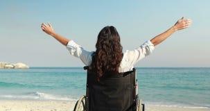 Donna disabile con le armi stese alla spiaggia video d archivio