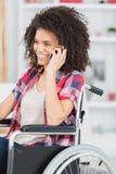 Donna disabile sulla sedia a rotelle facendo uso del telefono di mobil immagini stock