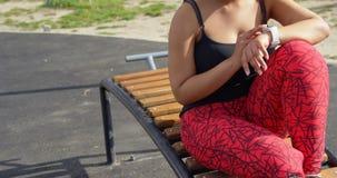 Donna disattivata facendo uso di smartwatch in parco un giorno soleggiato 4k video d archivio