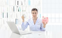 Donna dispiaciuta al computer con la carta di credito ed il porcellino salvadanaio immagine stock