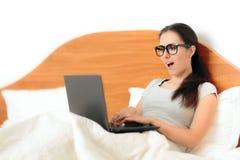 Donna divertente che lavora dalla casa sul suo computer portatile a letto Fotografia Stock Libera da Diritti