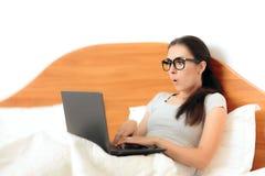 Donna divertente che lavora dalla casa sul suo computer portatile a letto Immagine Stock