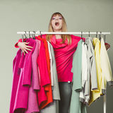 Donna divertente che prende tutti i vestiti in centro commerciale o in guardaroba Immagine Stock Libera da Diritti