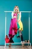 Donna divertente che prende tutti i vestiti in centro commerciale o in guardaroba Immagini Stock Libere da Diritti