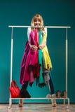 Donna divertente che prende tutti i vestiti in centro commerciale o in guardaroba Fotografie Stock