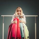Donna divertente che prende tutti i vestiti in centro commerciale o in guardaroba Fotografia Stock