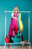 Donna divertente che prende tutti i vestiti in centro commerciale o in guardaroba Fotografie Stock Libere da Diritti