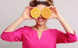Donna divertente che tiene le metà delle arance contro il fondo fotografie stock