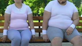 Donna divertente ed uomo grassi che si siedono sul banco, flirtante l'un l'altro, sensibilità video d archivio