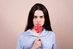 Donna divertente sveglia con la lecca-lecca a forma di del cuore fotografie stock libere da diritti