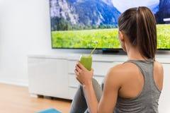 Donna domestica che beve frullato verde che guarda TV Immagine Stock Libera da Diritti