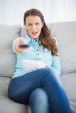 Donna dubbiosa che si siede sul canale televisivo cambiante del sofà Fotografia Stock