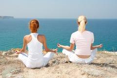 Donna due che meditating in montagne Fotografia Stock