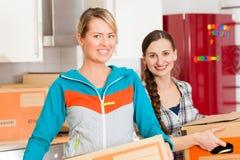 Donna due con la casella commovente nella sua casa Immagini Stock Libere da Diritti
