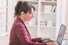 Donna dura d'udito che lavora con il computer portatile immagine stock libera da diritti