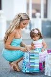 Donna durante l'acquisto con la bambina Immagine Stock