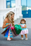 Donna durante l'acquisto con la bambina Fotografie Stock Libere da Diritti