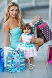 Donna durante l'acquisto con la bambina Immagini Stock Libere da Diritti