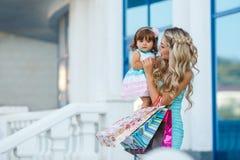Donna durante l'acquisto con la bambina Fotografia Stock