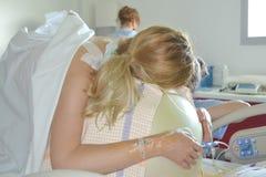 Donna durante le contrazioni su un parto della palla di forma fisica Immagini Stock