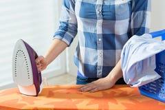 Donna durante rivestire di ferro dei vestiti immagine stock