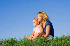 Donna e bambina all'aperto che si siedono Fotografie Stock