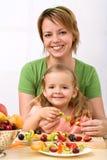 Donna e bambina che fanno il kebab della frutta fotografia stock libera da diritti