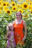 Donna e bambina sorridenti sul giacimento dei girasoli immagine stock libera da diritti