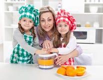 Donna e bambini che producono la spremuta della frutta fresca Fotografie Stock Libere da Diritti